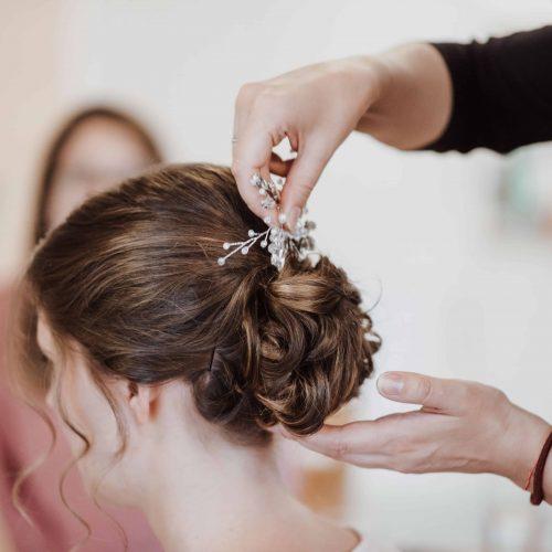 Frau mit Hochgesteckten Haaren bekommt einen Haarschmuck in ihre Braut Frisur gesteckt